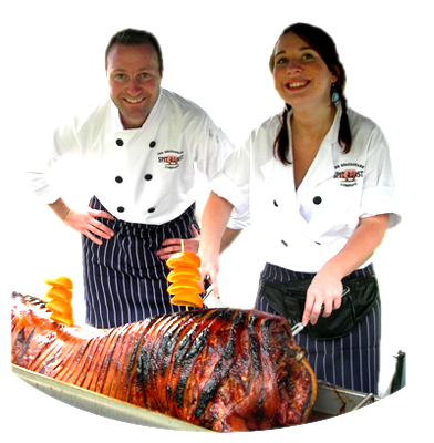 Two of our friendly chefs carving a Shakespeare Spit Roast!