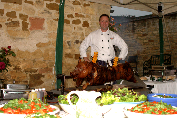 A spit-roasted pig sits on display behind an array of salads.