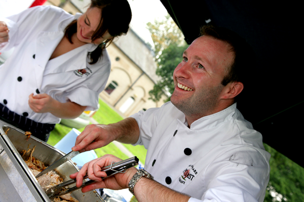 Two of our skilled chefs serve spit-roasted meat at the Leamington Spa Food Festival.